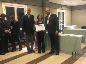 Aida Turquetto, que assina o trabalho vencedor entre os pôsteres, recebendo o certificado das mãos de Marcelo Jatene e Leonardo Miana